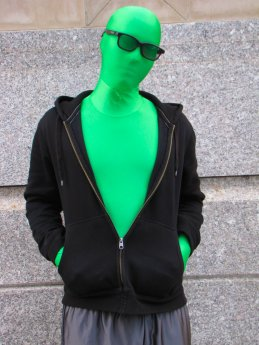 A man wears a green zentai suit with sunglasses, a hoodie, and shorts.