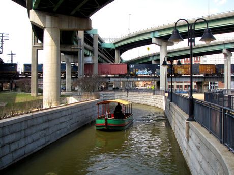 Bridges for the Downtown Expressway pass above, as a boat moves beneath in the Canal.
