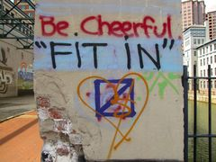 """""""Be cheerful, 'FIT IN'"""" graffiti on a column."""