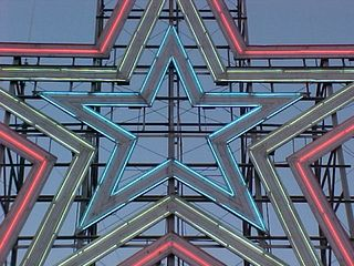 The lights are on, and the sky is blue. I love the way the star sits against the structure and the sky.