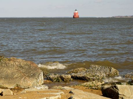Sandy Point Shoal Light, with rocks at the southeast corner of the park in the foreground.