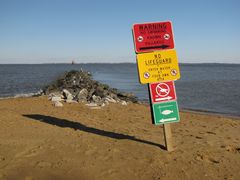 Warning signs ahead of a short rock jetty in the southeast corner of the park.