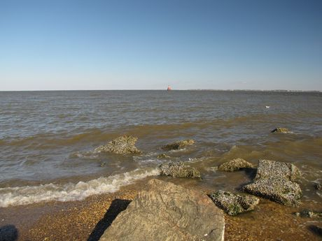 Rocks littering the beach at the water's edge. Sandy Point Shoal Light is visible in the distance.