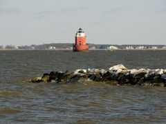 End of a rock jetty on the east side of the park. Sandy Point Shoal Light is visible in the distance.