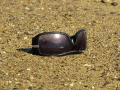Abandoned pair of sunglasses on the beach.