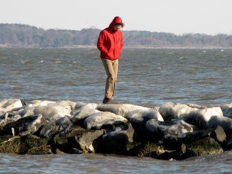A man walks on an ice-covered rock jetty at East Beach.