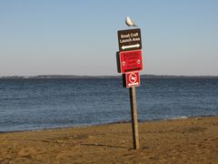 A bird perches on a sign at the southeast corner of the park.