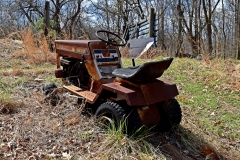 Rusted Sears Craftsman LT1036 lawnmower, in the yard north of the house