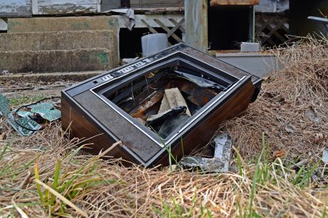Fisher Studio-Standard television, discarded and broken on the ground in front of the house