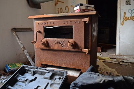 Rusted Kodiak wood-burning stove at the south end of the living room