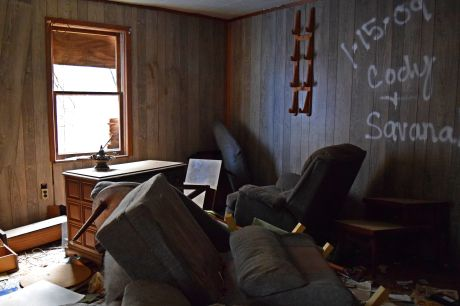 Family room, containing a broken out television set, as well as couches, now in disarray