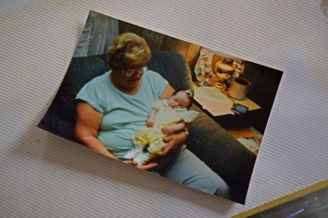Photograph showing an older woman holding an infant, taken in the family room