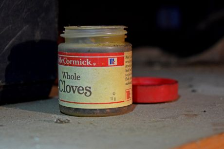 An opened container of McCormick whole cloves on a countertop