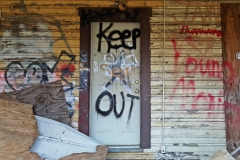"""Front door, with """"KEEP OUT"""" written on it in spray paint"""