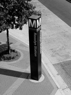 The street pylon at North Moore Street in Rosslyn casts a shadow onto the sidewalk as it marks the entrance to the Rosslyn Metro station.