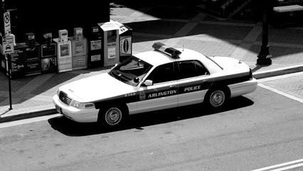 A police car sits parked next to the Metro elevator.