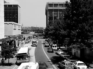 The volume of traffic on North Moore Street between midday and late night may change, but the row of taxicabs along the curb remains constant.
