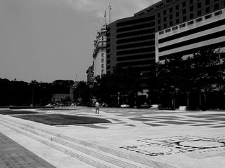 Meanwhile, a lone pedestrian strolls along Freedom Plaza's open expanse.