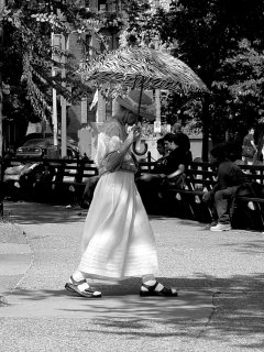 Another woman walking through Dupont Circle uses a zebra-striped umbrella to keep the sun off.