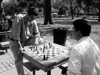 Two gentlemen were involved in a chess game along one side of the circle, thinking carefully between each move.