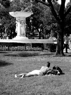 On the other side of the park, another man takes a moment to sunbathe, and also speak to a bicyclist passing by.