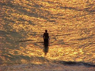 And as the sun gets up, a man plays in the surf.