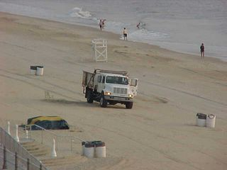 All right! The sun is out! People are starting to come out, and a dump truck is going across the sand...