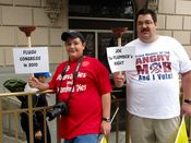 Two men hold plungers with plumbing-related signs.