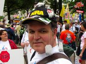 A man wears a hat decorated with Luzianne tea bags, symbolizing the Tea Party Movement.