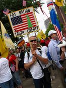 """A man holds a sign saying, """"Fox Nation, Truth, Liberty""""."""