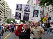 A woman holds a sign equating President Obama with Vladimir Lenin, Joseph Stalin, Adolf Hitler, and Fidel Castro.