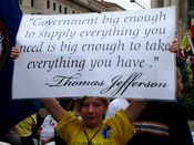 """A young woman holds a sign with a quote attributed to Thomas Jefferson, saying, """"Government big enough to supply everything you need is big enough to take everything you have."""""""