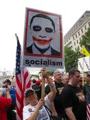 """A woman carries a sign showing the Barack Obama """"Joker"""" poster."""