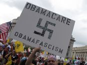 A man holds a sign comparing health care reform to fascism, using a right-facing swastika to symbolize this.