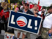 """A man holds a sign taking the Obama campaign's """"O"""" logo and making it part of the phrase, """"LOL!"""""""