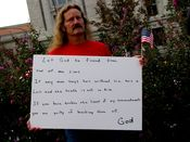 A man carries a small flag and holds a sign containing various Biblical quotations.