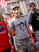 A man holds a flag while wearing a Guy Fawkes mask. I confirmed - his use of the mask had nothing to do with any anti-Scientology stance (DC Anons had considered trolling the event).