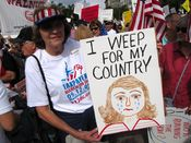 """A woman holds a sign reading, """"I weep for my country."""""""