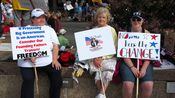 Three women sit on the wall around Freedom Plaza holding signs.