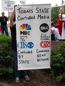 """A man holds up a banner accusing various media organizations of being state-controlled. Note misspelling of """"Barack"""" next to the ABC logo."""