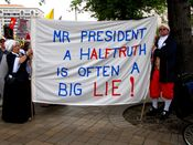 """A couple dressed in such a way to resemble colonial attire holds a banner reading, """"Mr. President, a half truth is often a BIG LIE!"""""""