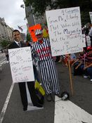 A man wearing a striped uniform and a ball and chain holds signs and an Obama cutout accusing the President and Congress of elitism and catering to special interests.