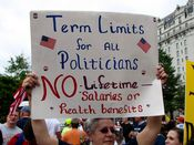 A woman holds a sign advocating term limits for all politicians.