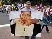 A man holds a sign showing President Obama tearing up the Constitution.
