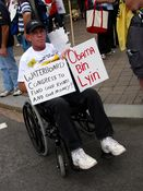 """A man holds signs advocating waterboarding Congress, and referring to President Obama as """"Obama Bin Lyin'""""."""