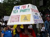 """A man holds a four-sided sign, reading """"Time For A Tea Party"""" on one side, and """"Stop spending and legalize the Constitution"""" on another."""