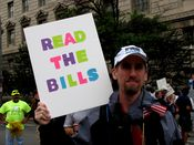 """A man holds a sign saying """"Read the bills"""". At this time, there were multiple bills for health care reform on Congress's plate, and so the signmaker deserves credit for noting this."""