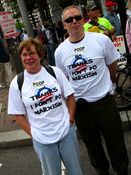 """A couple wears shirts that say, """"No thanks, I don't do Marxism"""", and stickers that say, """"POOP: Prisoners of Obama's Policies""""."""