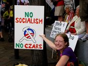 """A woman holds up a sign that combines the Obama """"O"""" logo with the hammer and sickle, with the words, """"No socialism, no czars"""" around it. It should be noted, however, that the Russian czars were not communists."""