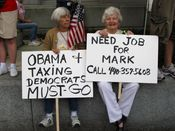 Two women hold signs while sitting on a wall next to the John A. Wilson Building. It is worth noting that the phone number on the sign that the woman on the right is holding is apparently a legitimate phone number, going to a residence in Painesville, Ohio.